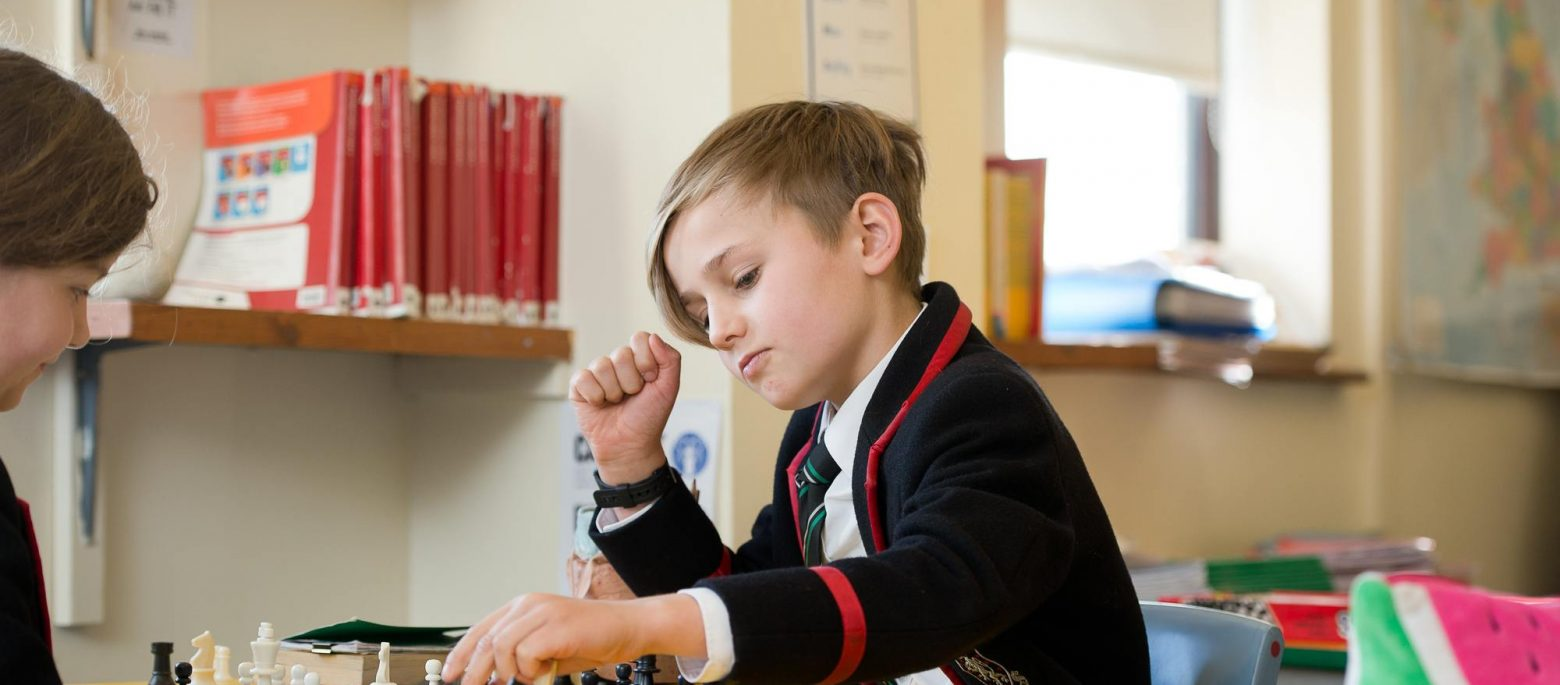A young boy moves a chess piece on the board