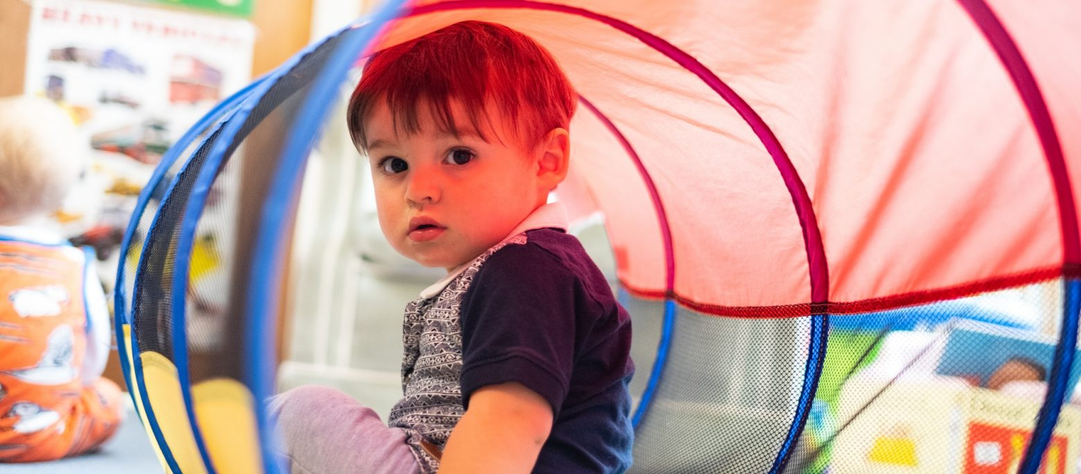A young boy in a plastic tunnel as they're enjoying play time