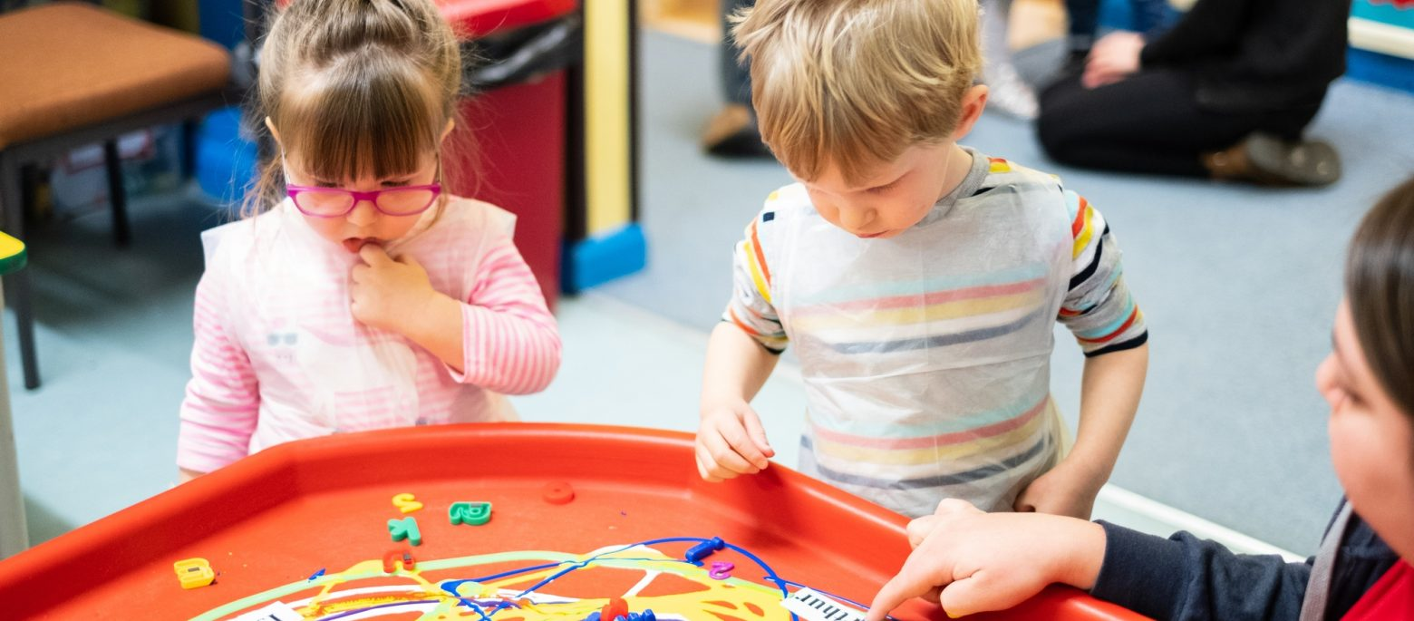 School children playing a game with plastic letters