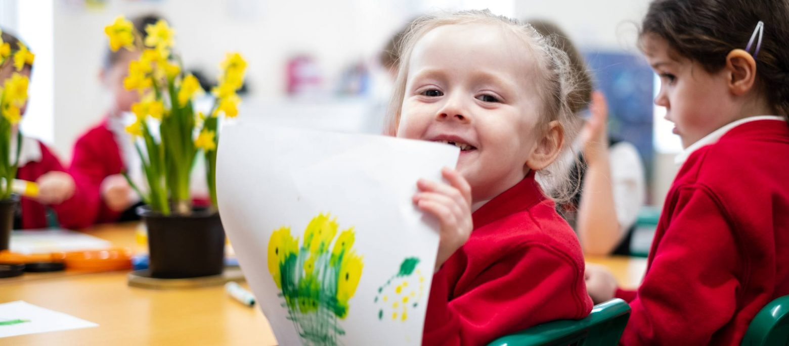 A smiling girl holding up a painting she's done of some daffodils