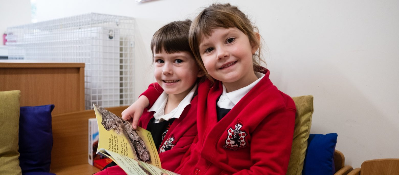 2 girls reading a book together