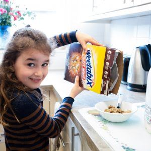 A girl pouring cereal into her bowl