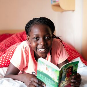 A girl smiling as she reads her book