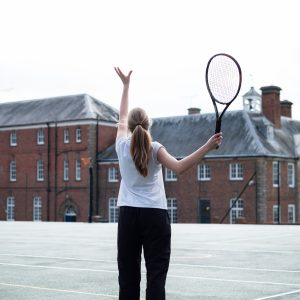 A young school girl playing tennis