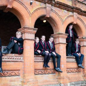 Lucton School children sitting in arches of red brick building