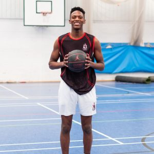 A student smiles as he's holding a basketball