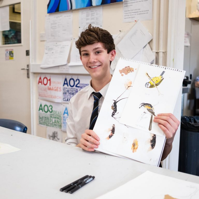 A young school boy showing his many drawings of birds for an art project