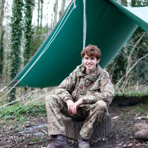 Child in cadet uniform outside a tent