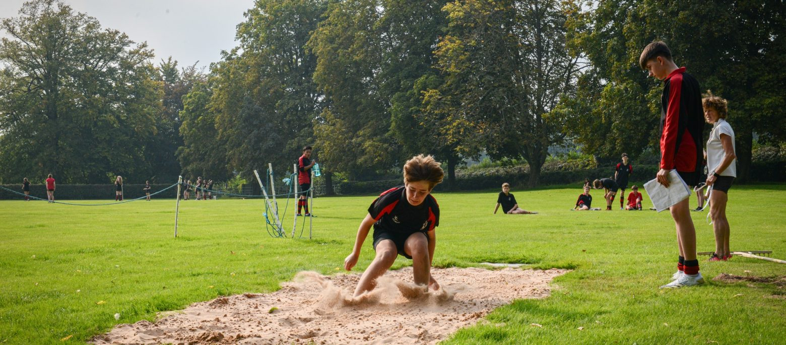 A young boy jumping into the sand