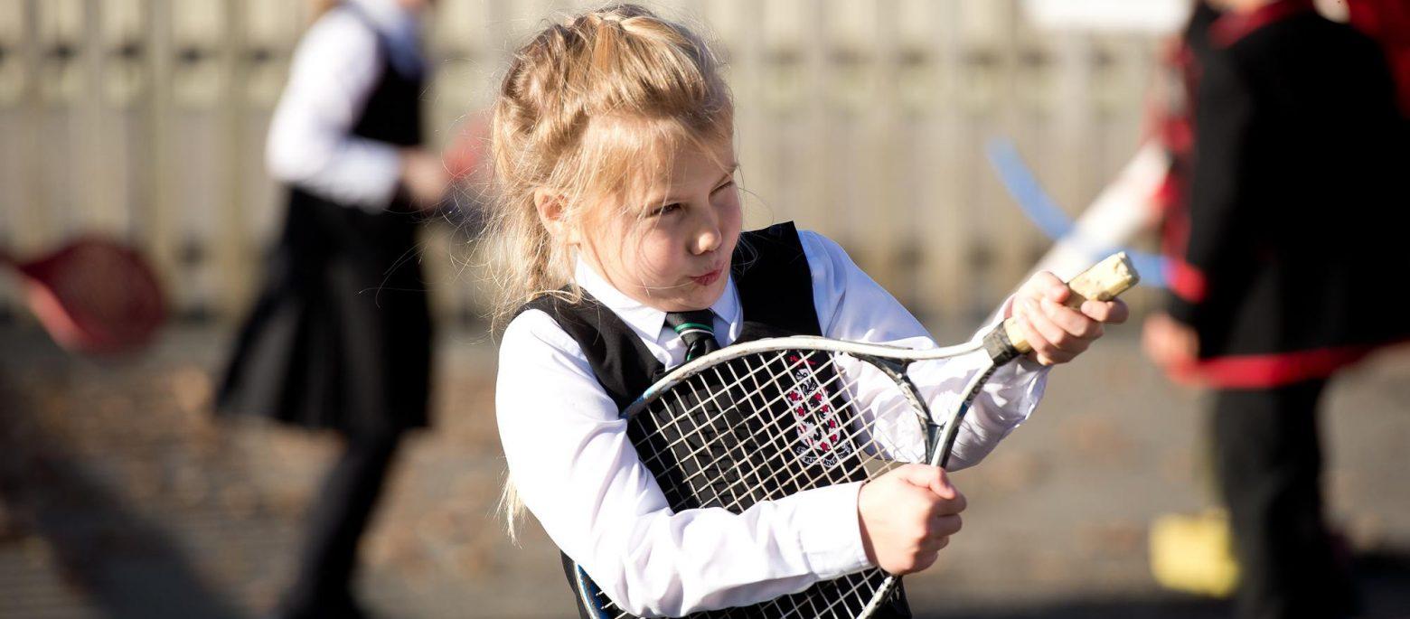 school girl holding tennis racket