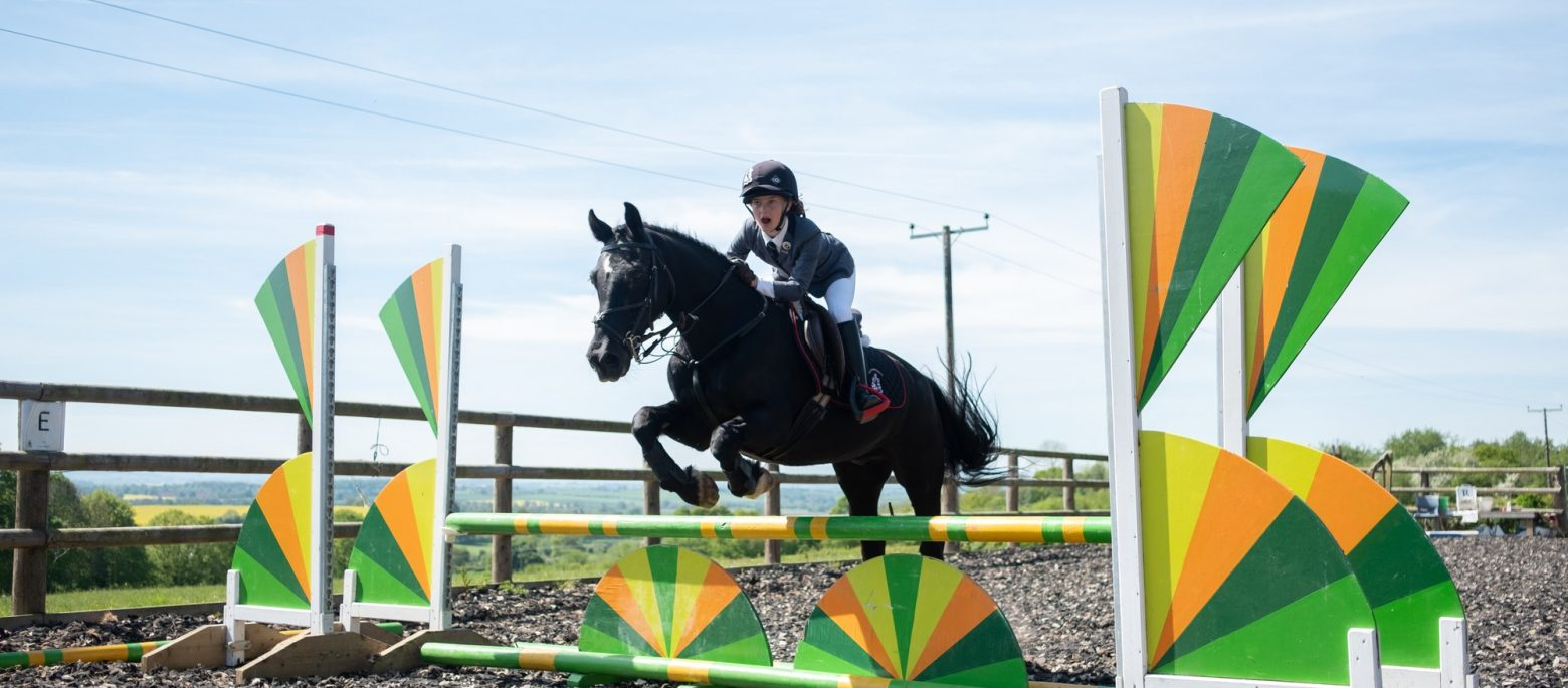 A girl and her horse jumping over a hurdle