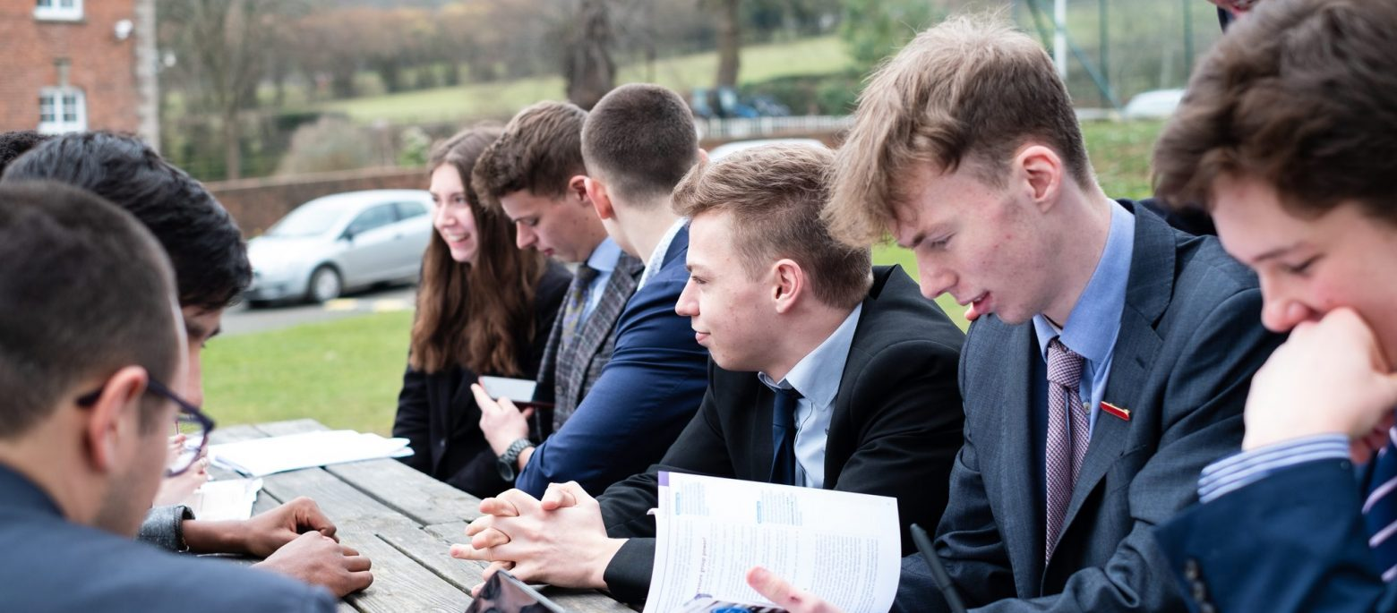 Lucton School students sitting outdoors at a picnic table