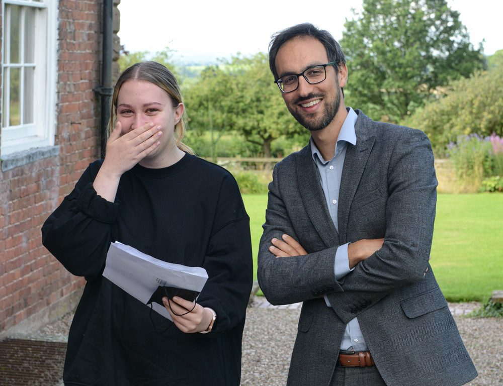 A happy girl smiling at her A Level results with a teacher stood next to her