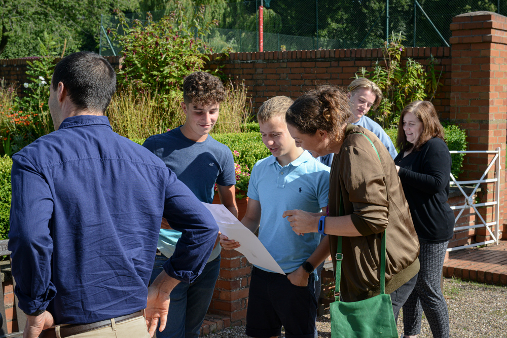 Students happily look at their GCSE results with their parents